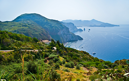 Lipari Island boasts its lush vegetation because of reach volcanic soils and indented coastline with a view on the smoking crater of Volcano Island, Aeolian Islands, Italy.