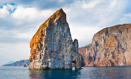The indented coastline of Lipari Island makes it very popular for the tourists and lonely rocks in sea are the visit cards of the island, Aeolian islands, Italy. Stock Photo