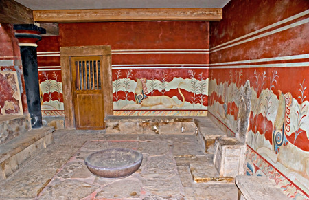 HERAKLION, GREECE - OCTOBER 13, 2013: The unique decorated chamber named the Throne Room with the stone throne and griffon frescos on the walls, Knossos Palace, on October 13 in Heraklion. photo