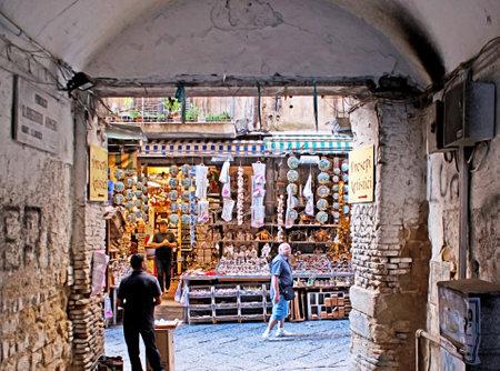 NAPLES, ITALY - OCTOBER 3, 2012: The big souvenir market on Via San Gregorio Armeno, view from the narrow dusty backstreet, on October 3 in Naples.