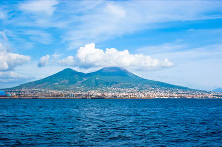 The ancient Mount Vesuvius rests on the seashore of the Gulf of Naples in the beautiful hat of the white clouds, Italy.