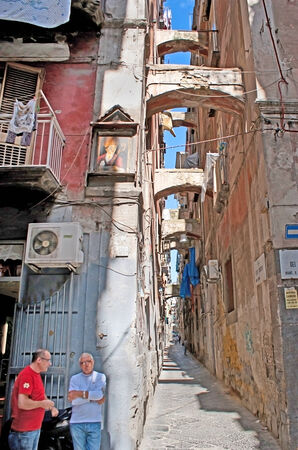 struts: NAPLES, ITALY - OCTOBER 3, 2012: The narrow street with high ramshackle houses, supported by struts between them, decorated by the old icon on the wall, on October 3 in Naples. Editorial