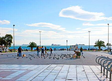 THESSALONIKI, GREECE - OCTOBER 17, 2013: People feed the doves on the Aristotle Square located next to the Nikis avenue (on the citys waterfront), on October 17 in Thessaloniki.