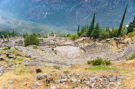 The ancient theatre of Delphi located on the picturesque slope with a view on the Appolo Temple, Athenian Treasury and the olive-wood valley, Greece. photo
