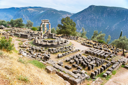 ancient greece: The sanctuary of Athena Pronoia with its restored Tholos surrounded by Parnassus mountains, Delphi, Greece.