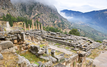 DELPHI, GREECE - OCTOBER 10, 2013: The  ruins of ancient temple of Apollo and Parnassus mountains on the background, on October 10 in Delphi.