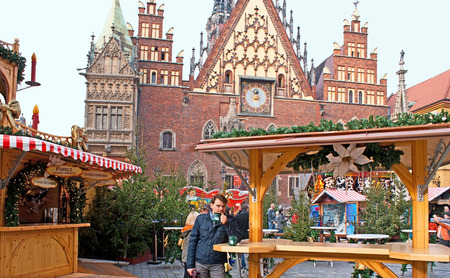 WROCLAW, POLAND - NOVEMBER 24, 2012: The tourist drinks hot wine in the street cafe during the Christmas Fair on the Marketplace, with the Christmas trees bazaar on the background, on November 24 in Wroclaw.