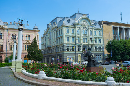chernivtsi: CHERNIVTSI, UKRAINE - JUNE 20, 2014: The  monument to Olha Kobylanska, famous ukrainian writer with the Regional Palace of Culture and the Jewish peoples house on the background, on June 20, 2014.