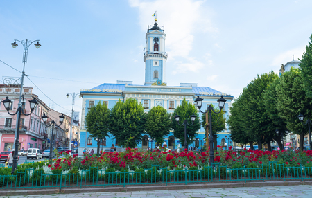 central square: CHERNIVTSI, UKRAINE - JUNE 20, 2014: The green trees and scenic flower beds with red roses located on the foreground of the Town Hall on the Central Square, on June 20, 2014.