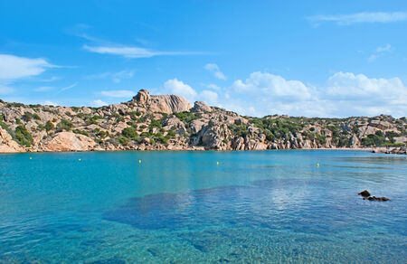 shores: The small scenic harbor  of Cala Spalmatore, with bright blue waters, rocky shores and cozy sand beach, Maddalena Island, Sardinia, Italy.