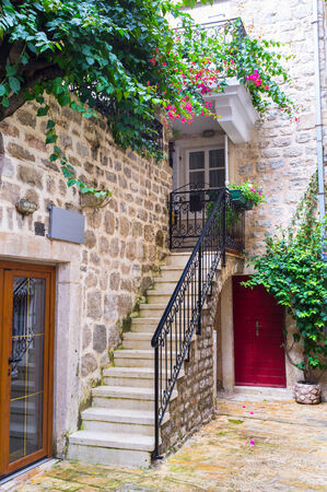 BUDVA, MONTENEGRO - JULY 12, 2014: The tiny staircase leads to the old house, decorated with green plants, on July 12 in Budva.
