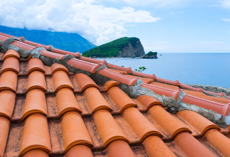 The view on the Sveti Nikola Island over the tile roof of the citadel, Budva, Montenegro. photo