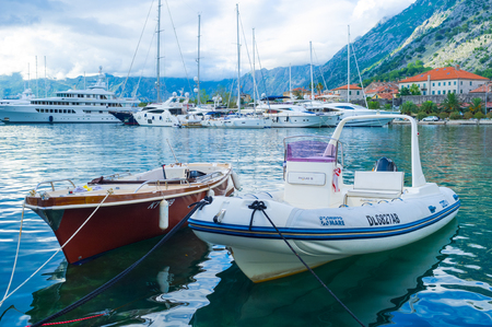 KOTOR, MONTENEGRO - JULY 12, 2014: The small boats with the large luxury yachts on the background, on July 12 in Kotor.