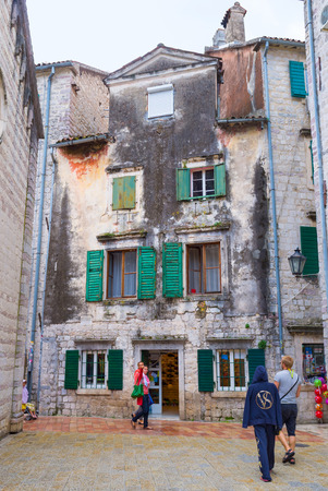 KOTOR, MONTENEGRO - JULY 12, 2014: The medieval streets of Stari Grad are full of old houses with crumbling plaster and craquelure paint, on July 12 in Kotor.
