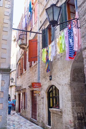 KOTOR, MONTENEGRO - JULY 12, 2014: The grey stone town became colorful because of different drying clothes, on July 12 in Kotor.