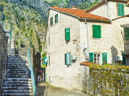 The narrow street located under the mountain with the staircase to the medieval ramparts, surrounding the old town, in Kotor. photo