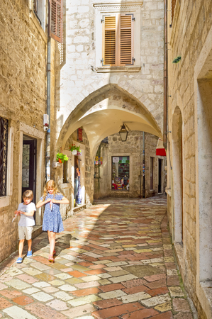 KOTOR, MONTENEGRO - JULY 12, 2014: Children walk on the medieval street after the hard rain, on July 12 in Kotor.