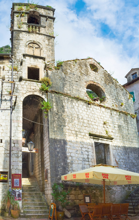KOTOR, MONTENEGRO - JULY 12, 2014: The ruins of the medieval church became the shelter for the street cafe, on July 12 in Kotor.