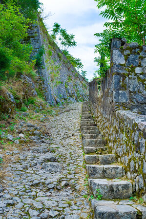 The old narrow stairs and the bumpy stone road leads to the fortress of St John, located above the medieval town of Kotor, Montenegro. photo