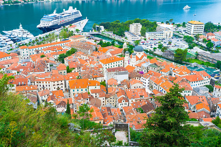 The mountains over the Kotor bay overlooks the old town, port, the shipyard with yachts and cruise liners, Kotor, Montenegro. photo