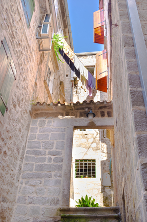 The entrance to the medieval house with the tiny courtyard and drying clothes, Kotor, Montenegro. photo