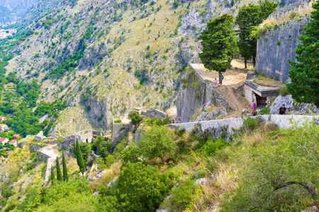 KOTOR, MONTENEGRO - JULY 15, 2014: The tourists relax after the long climbing to the medieval fortress of St John, located in mountains, on July 15 in Kotor.