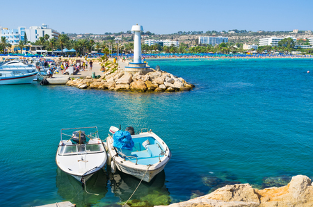The port of Ayia Napa with the couple of moored boats and the view on the busy beaches on the background, Cyprus. Publikacyjne