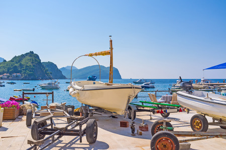 boat trailer: The small fishing boat stands on the boat trailer on the embankment of the small harbor of Petrovac, Montenegro. Editorial