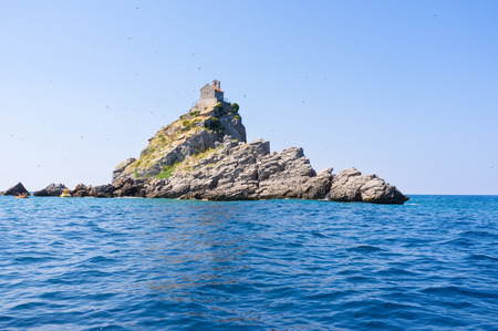 The Church of Sveta Nedelja located on the rocky island of Mali Katic, next to the coast of Petrovac, Montenegro. photo