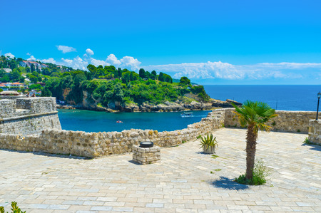 The Kalaja castle overlooks the coastline of Ulcinj and rocky cliffs covered with forest, Montenegro. photo