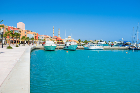 The bright blue waters of the Red sea surrounded by the modern colorful buildings of Marina, Hurghada, Egypt.