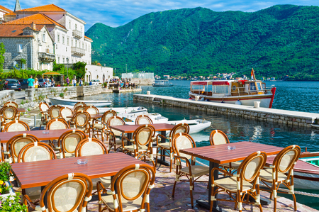 The Marina of Perast is the best place for outdoor cafe, visitors enjoy the medieval architecture, high mountains, fresh sea air and the scenic boats, Montenegro.