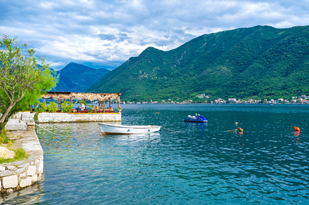 The old cafe on the water is the favorite tourist place with delicious local cuisine and nice view on Kotor bay, Perast, Montenegro.