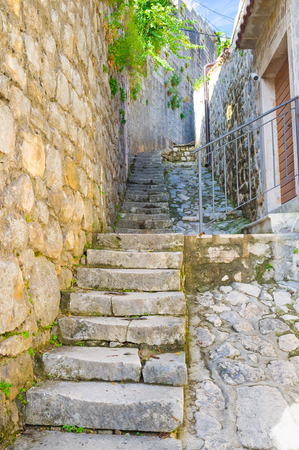 The old stone stairs on the hilly street and the high wall, going to the top, Perast, Montenegro. photo