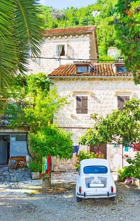 The tiny garden in front of the house with the retro car, parked in the yard, Perast, Montenegro.