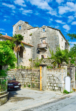 The medieval streets of Perast are full of old villas, surrounded by stone fences, Montenegro.
