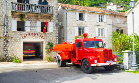 PERAST, MONTENEGRO - JULY 13, 2014: The bright red retro fire truck parked in the yard of the fire station, located on the city promenade, on July 13 in Perast.