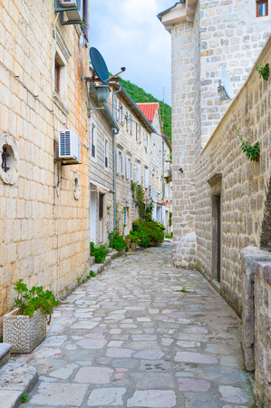 The narrow winding streetwith white stone houses, located at the foot of the mountain, Perast, Montenegro.