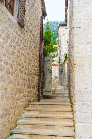 The old town located at the foot of the mountain, so there are many narrow streets with the old staircases, going up, Perast, Montenegro.