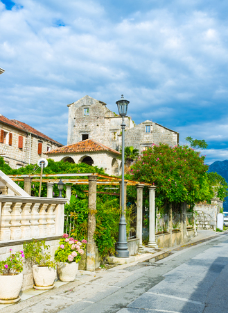 The old buildings and the lush gardens on the  promenade of Perast, Montenegro.