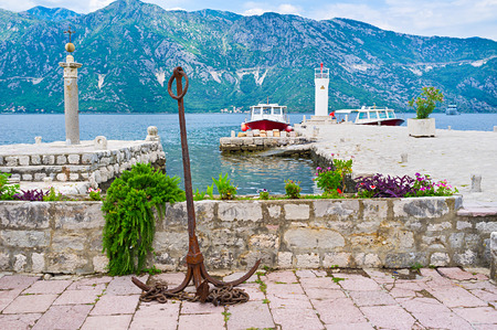 The rusty anchor set as the decoration on Our Lady of the Rocks islet next to the tiny harbor for tourist boats, Perast, Montenegro. photo