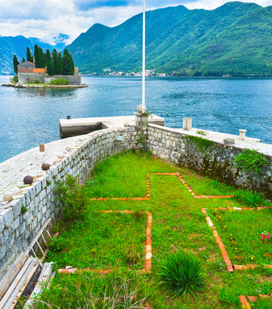 The flower bed on Our Lady of the Rocks islet with the old stone fence looks like the bow of the ship, Perast, Montenegro. photo