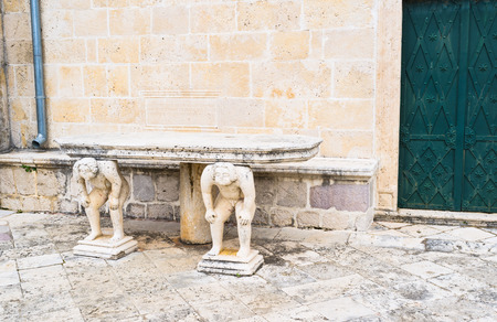 The medieval stone table is supported by two statues of the hunched men, standing next to the side entrance to Our Lady of the Rocks basilica, Perast, Montenegro. photo