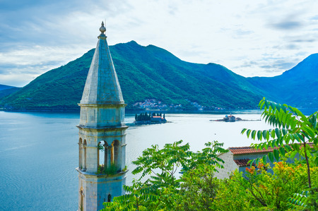 The medieval bell tower of St Antony's Church with two islets of the Kotor Bay on the background, Montenegro.