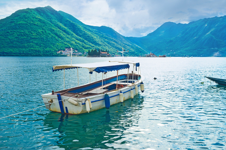 The white tourist boat with two islets on the background, Perast, Montenegro. photo