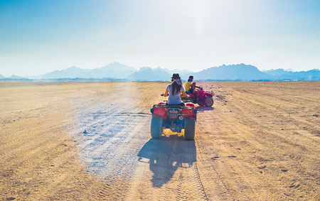 The tourists ride on quads through the Sahara desert to the Bedouin village, Egypt.