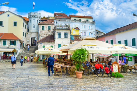 HERCEG NOVI, MONTENEGRO - JULY 13, 2014: The old town gate with the small clock tower surrounded by old houses, cafes and bars, on July 13 in Herceg Novi. Publikacyjne