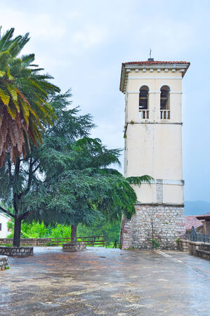 The bell tower of St Jerome Church surrounded by lush green trees on the tiny square, Herceg Novi, Montenegro. photo
