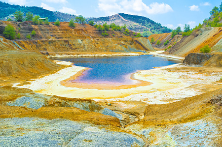 sulfide: The mine lake has the banks covered with the sulphur crystals yellow, orange and red colors, Sia, Cyprus.