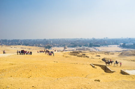chephren: Tourists climb to the hill to see the Great Pyramids in Giza Necropolis, Egypt.